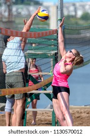 Saint John, New Brunswick, Canada - July 1, 2018: Beach vollyball by Market Square. A man spikes a vollyball over the net as a woman blocks it.