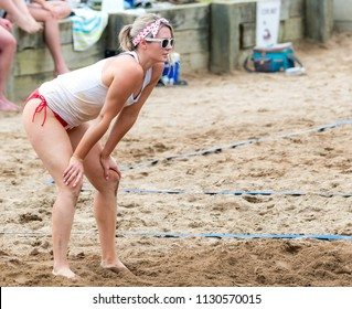 Saint John, New Brunswick, Canada - July 1, 2018: Beach vollyball by Market Square. A woman crouches ready as she waits for the ball to be served.