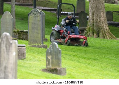 Saint John, New Brunswick, Canada - July 25, 2018: A man using a riding lawn mower to mow the lawn in a grave yard.