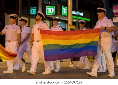 Saint John, New Brunswick, Canada - August 11, 2018: Naval personnel participate in the annual LGBT Pride Parade. They are carrying a rainbow flag.