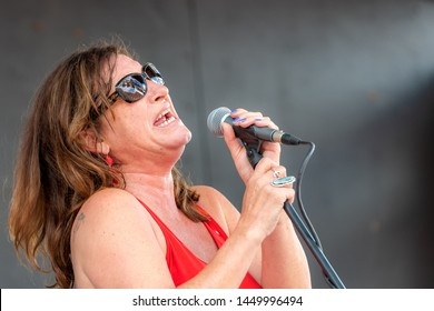 Saint John, New Brunswick, Canada - July 1, 2019: A woman sings in a free, outdoor, public concert as part of Canada Day celebrations. She is wearing sunglasses and holding a microphone in a stand.