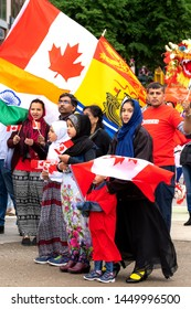 Saint John, New Brunswick, Canada - July 1, 2019: Members of the Muslim community participate in the Canada Day parade. Canada and New Brunswick flags visible.