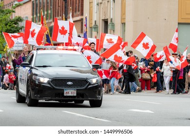Saint John, New Brunswick, Canada - July 1, 2019: A police car leads the Canada Day parade. Many people with Canadian flags follow.
