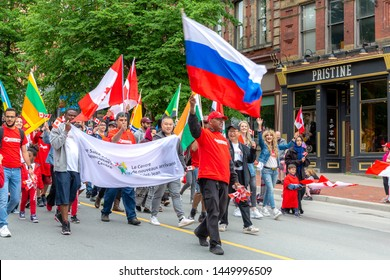 Saint John, New Brunswick, Canada - July 1, 2019: A man from the Saint John Newcomers Centre carries a Russian flag in the Canada Day parade. Other people with various flags accompany him.