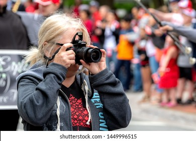 Saint John, New Brunswick, Canada - July 1, 2019: An amateur photographer take a photo at the Canada Day parade using a Nikon camera.
