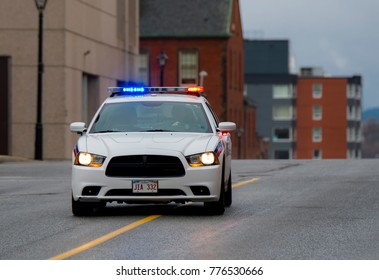 Saint John, New Brunswick, Canada - November 26, 2017: A police car with its red and blue lights on travels at high speed down the center of a city street.