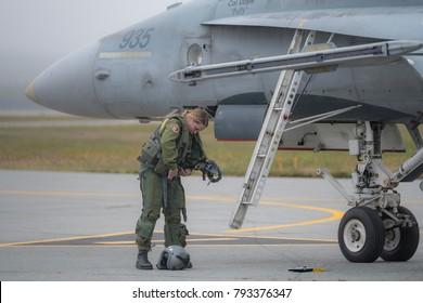 Saint John, New Brunswick, Canada - Setpember 17, 2017: A female fighter pilot preperes her flight suit standing next to a CF-18 Hornet fighter jet.