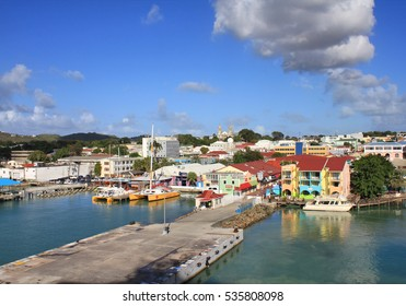 SAINT JOHN'S, ANTIGUA - FEBRUARY 19, 2014: Waterfront with pier and colorful houses in St John's, Antigua and Barbuda. Antigua is a popular destination for cruise ships
