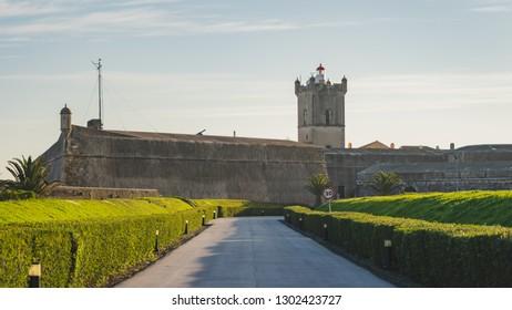 Saint Julian Fortress (Forte de Sao Juliao da Barra) entrance with green garden, tower, and lighthouse, road with tony lampposts, Oeiras, Lisbon