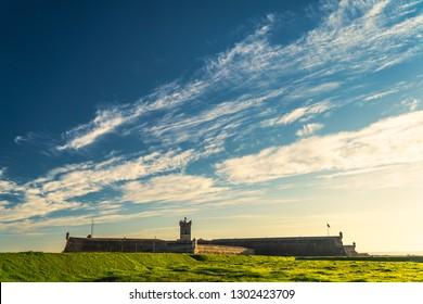 Saint Julian Fortress lighthouse tower standing behind empty land with green grass Oeiras, Lisbon