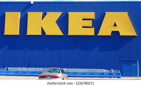 Saint Laurent, Quebec/Canada - September 19, 2012 : Iconic Ikea yellow sign on blue building in front of row of shopping carts and one single car