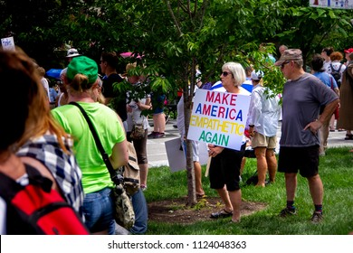 Saint Louis, MO—June 29, 2018; woman holding political speech sign at rally in public park. Democrat organizations protested immigration policy in St. Louis on June 29.