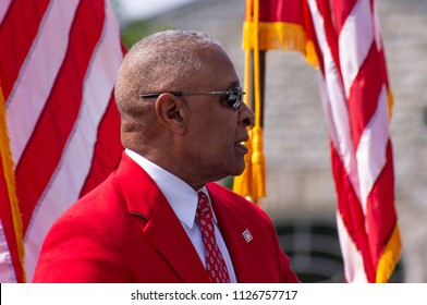Saint Louis, M)—July, 3, 2018; former Saint Louis Cardinal shortstop Ozzie Smith sitting on stage with flags in background at grand opening of Gateway Arch National Park and Museum