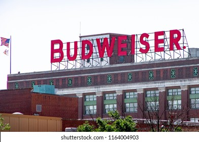 """Saint Louis, MO—Aug 4, 2018; Large marque sign above brick factory in capital red letters spells """"BUDWEISER"""" marks the Anheuser Busch beer brewery."""