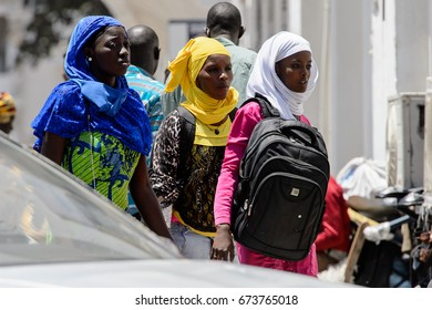 SAINT LOUIS, SENEGAL - APR 24, 2017: Unidentified Senegalese people walk along the street in the centre of Saint Louis, one of the major cities in Senegal