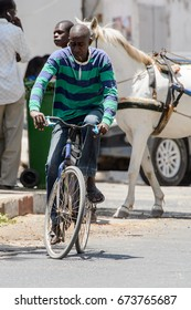 SAINT LOUIS, SENEGAL - APR 24, 2017: Unidentified Senegalese man rides a bicycle in the centre of Saint Louis, one of the major cities in Senegal