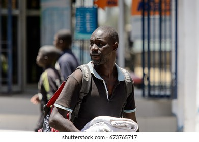 SAINT LOUIS, SENEGAL - APR 24, 2017: Unidentified Senegalese man with backpack walks along the street in the centre of Saint Louis, one of the major cities in Senegal