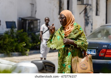 SAINT LOUIS, SENEGAL - APR 24, 2017: Unidentified Senegalese woman in glasses and traditional clothes walks along the street in the centre of Saint Louis, one of the major cities in Senegal