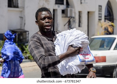 SAINT LOUIS, SENEGAL - APR 24, 2017: Unidentified Senegalese man walks along the street with goods for sale in the centre of Saint Louis, one of the major cities in Senegal