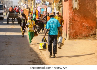SAINT LOUIS, SENEGAL - APR 24, 2017: Unidentified Senegalese man carries a bucket beside the road in Saint Louis, one of the biggest cities in Senegal