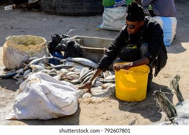 SAINT LOUIS, SENEGAL - APR 24, 2017: Unidentified Senegalese man in sunglasses and black clothes sells fish at the local market of Saint Louis, Senegal