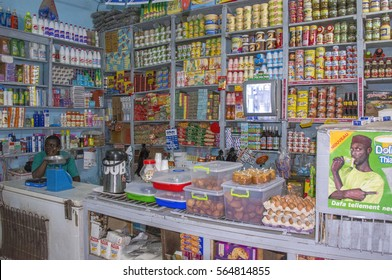 SAINT LOUIS, SENEGAL - MAY 28, 2014: Typical grocery store, open at night, full of shelves with products and an employee sitting in a corner