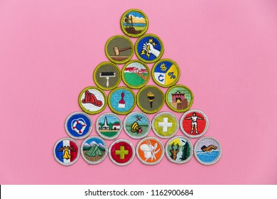 SAINT LOUIS, UNITED STATES - AUG 22, 2018:  A geometric arrangement of Boy Scouts of America (BSA) merit badges on pink background as BSA welcomes girls to join scouting