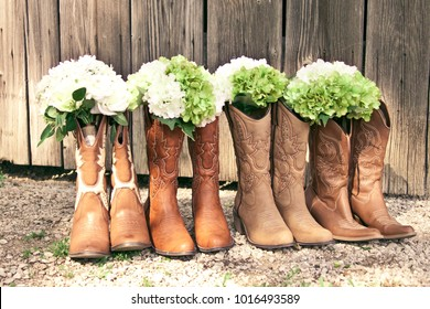 SAINT LOUIS, UNITED STATES - MAY 31 2014: Cowboy boots and bridesmaid bouquets are lined up by a grey barn at a country theme wedding