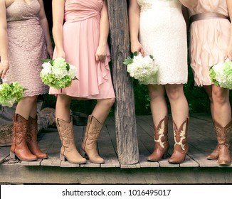 SAINT LOUIS, UNITED STATES - MAY 31 2014:  Four bridesmaids with bouquets and wearing cowboy boots at a country themed wedding