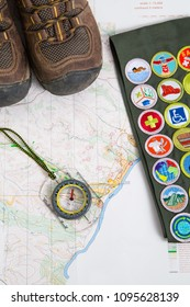 SAINT LOUIS, UNITED STATES - MAY 3, 2018:  Hiking boots, a compass, and a BSA merit badge sash rest on a map ready for a hike