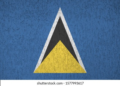 Saint Lucia flag depicted in bright paint colors on old relief plastering wall. Textured banner on rough background