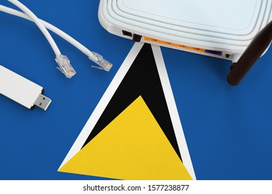 Saint Lucia flag depicted on table with internet rj45 cable, wireless usb wifi adapter and router. Internet connection concept