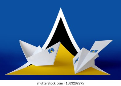 Saint Lucia flag depicted on paper origami airplane and boat. Handmade arts concept