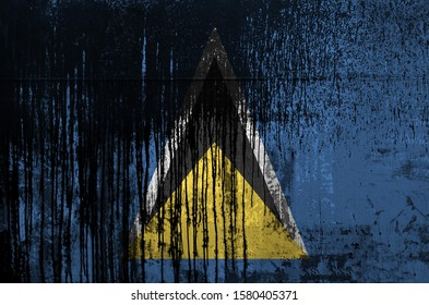Saint Lucia flag depicted in paint colors on old and dirty oil barrel wall closeup. Textured banner on rough background