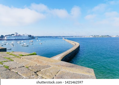 Saint Malo, France - May 21 2019: Early morning in Saint Malo, looking down from the city walls and out along the curved breakwater. In the harbour a  ferry is moored along with smaller boats.