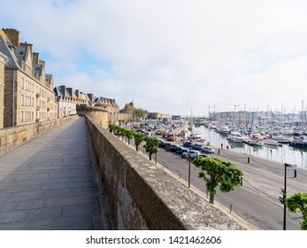 Saint Malo, France - May 21 2019: Standing on the city walls of Saint Malo. Cars are parked on the quayside and boats are moored in the harbour. In the far distance a lady walks her dog.