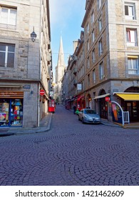 Saint Malo, France - May 21 2019: Early morning looking up Grande Rue in St Malo towards the Cathedral. A car is parked at the bottom of Grande Rue while two men stand talking outside a bar.