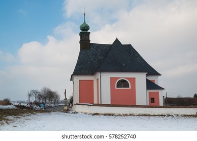 Saint Marco church in Kninice, Czech Republic Christian church in village Kninice in Moravia, Czech republic. Snow on the field. Intense cloudy sky. Green tower of the church.