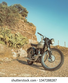 Saint Marinella, Rome, Italy -  09 10 2019: a beautiful vintage Norton parked on a mediterranean coast. Chrome tank. Rocks, pine trees and cactus in the background