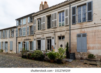 Saint Martin de Re, France - August 7, 2018: Street with restaurant and traditional old houses in Saint Martin de Re. Island of Re