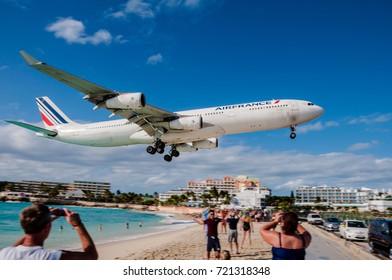Saint Martin, Netherlands Antilles- 12/22/2012 - Tourists taking photos as an Air France airplane lands at Princess Juliana Airport in St. Martin