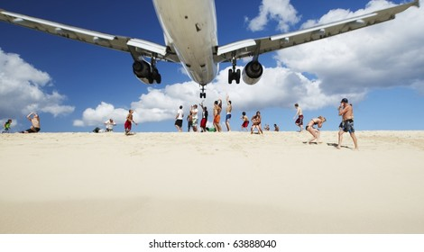 SAINT MARTIN, NETHERLANDS ANTILLES - APRIL 4: Maho beach near Princess Juliana International Airport. The airplane arrives over the full beach on April 4, 2010 in Saint Martin.