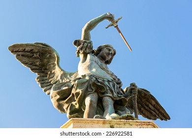 Saint Michael statue at the top of Castel Sant`Angelo, Rome, Italy. This castle is a landmark of Rome. Archangel with sword on the blue sky background. Low angle view of winged angel in Rome center.