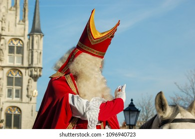Saint Nicholas waving on his white horse. In the background the old Stadhuys of Gouda. The Netherlands.