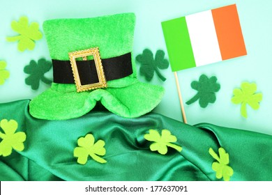 Saint Patrick day hat with clover leaves and Irish flag on green background