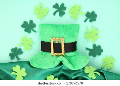 Saint Patrick day hat with clover leaves on green background