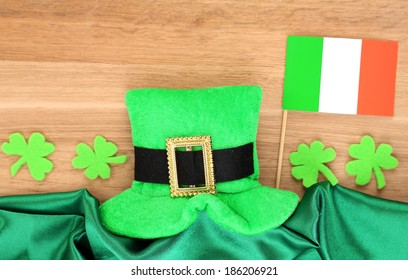 Saint Patrick day hat with clover leaves and Irish flag on wooden background