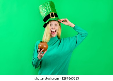 Saint Patrick's Day. Green top hat. Girl in green top hat holds pot with gold. Leprechaun. Green leprechaun. Green hat with clover. Irish Traditions. Leprechaun costume. Pot with gold.