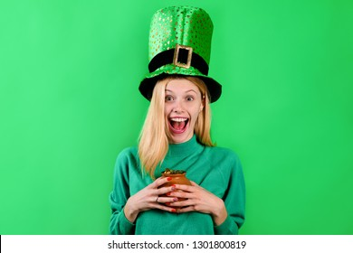 Saint Patrick's Day. Happy girl in green top hat holds pot with gold. Leprechaun. Irish Traditions. Green top hat. Green hat with clover. Clover. Patrick's Day. Pot with gold. Gold.