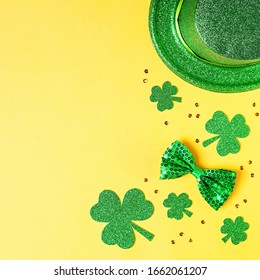 Saint Patrick's day holiday card with green shamrock symbols, hat, golden confetti. Traditional St. Patrick's Day green attire and decorations on yellow background.